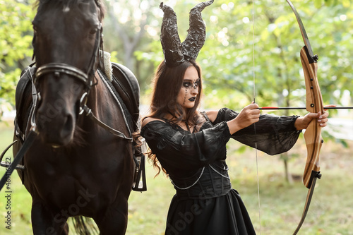 Foto Beautiful woman dressed for Halloween with bow in forest