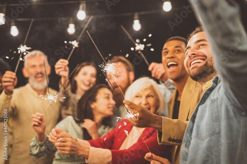 Obraz na plátně Family and friends celebrating at dinner on a rooftop terrace