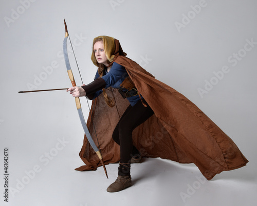 Fotografie, Obraz Full length, portrait of red haired woman wearing medieval viking inspired costume and flowing cloak,  Holding bow an arrow weapon,  posing against studio background