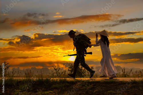 Fototapeta Silhouette soldier holding gun and  hold hand runing with his girl friend,girl wearing vietnam dresses and hat with sunsky background