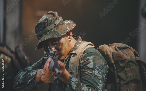 Fotografia Soldier action with gun on hand holding to protect, survey around safety area in soldier mission with white smoke background