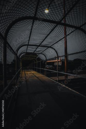 Fotografiet Empty caged footbridge at night