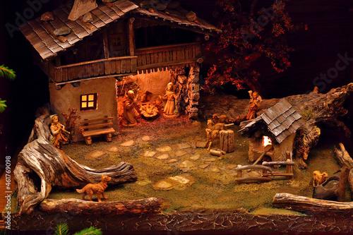 Fototapeta Still of a home made carved manger depicting the birth of Jesus Christ in dark l