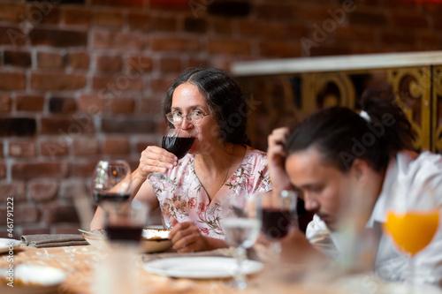 Obraz na plátne Woman having a glass of wine at family celebration in restaurant