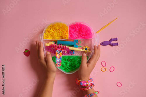 Valokuva Multicolored rubber bands for weaving bracelets in a heart-shaped box is held by a child