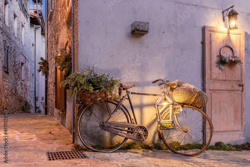 Fotografering Beautiful shot of a decorative bicycle in an illuminated vintage alleyway