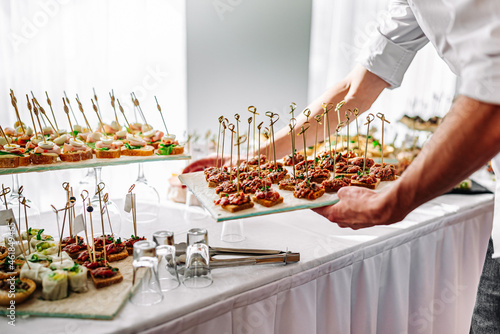 Tela hands of a waiter prepare food for a buffet table in a restaurant