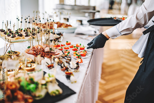 Fotografia female hands of a waiter prepare food for a buffet table in a restaurant