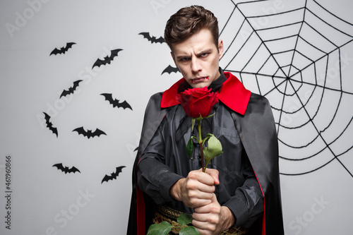 Fototapeta Vampire Halloween Concept - Portrait of handsome caucasian Vampire holding red beautiful rose