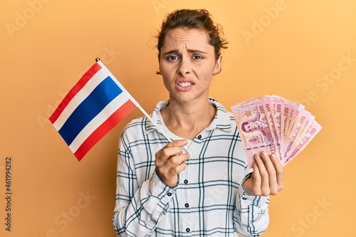 Fototapeta Young brunette woman holding thailand flag and baht banknotes clueless and confused expression
