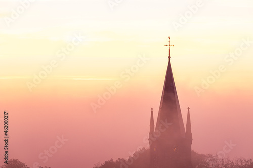 A typical colorful Autumn sunrise in Maastricht with the landscape covered with a layer of fog, leaving only silhouettes visible in the distance, like this tower of a church on the hillside Fotobehang