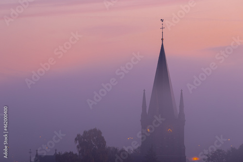 Canvas A typical colorful Autumn sunrise in Maastricht with the landscape covered with a layer of fog, leaving only silhouettes visible in the distance, like this tower of a church on the hillside