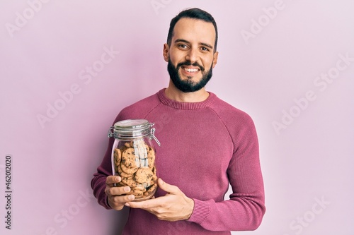 Fotografie, Obraz Young man with beard holding jar of chocolate chips cookies looking positive and