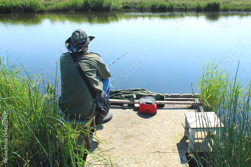 A fisherman with a fishing rod sits on the bank of the river, rear view Fotobehang