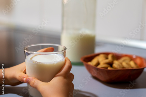 Fotografering Child's hands grabbing a glass glass with milk next to a jar with cookies and a bottle on the kitchen counter