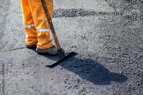 Fototapeta Road construction worker leveling fresh asphalt pavement