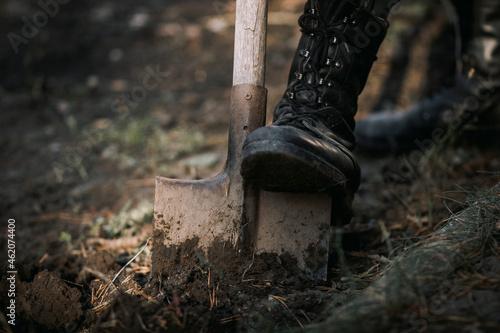 Fotografia A man's leg in a military boot and a bayonet shovel