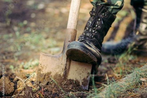 A man's leg in a military boot and a bayonet shovel Fotobehang