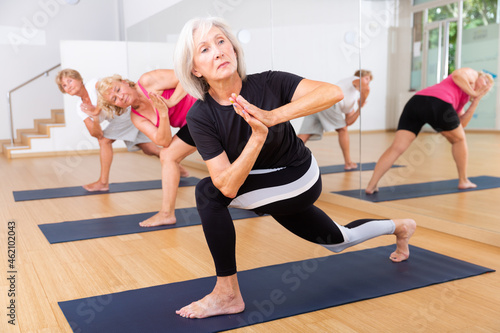 Canvas Mature women practicing yoga perform the exercise in the twisted side angle pose