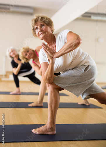 Mature women practicing yoga perform the exercise in the twisted side angle pose Fotobehang