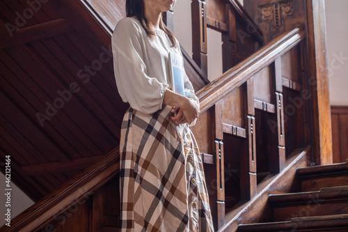 Murais de parede 本を持つ女性  レトロな建物に佇む女性  階段で本を持って立つ人