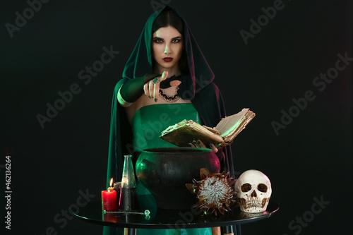 Obraz na plátně Witch performing ritual on black background