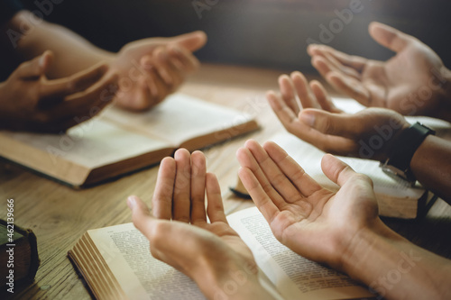 Fototapeta Christian group of people holding hands praying worship to believe and Bible on a wooden table for devotional or prayer meeting concept