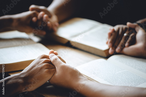 Christian group of people holding hands praying worship to believe and Bible on a wooden table for devotional or prayer meeting concept Fototapete