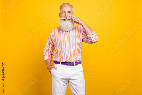 Photo of positive bearded old man shiny smile hand pocket wear striped shirt isolated yellow color background