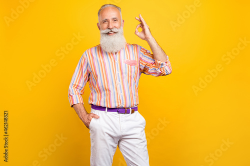 Photo of reliable pensioner promoter show okey gesture wear striped shirt isolated yellow color background
