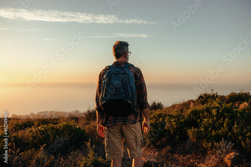 Fotografie, Obraz Anonymous backpacker looking at the view on a hilltop