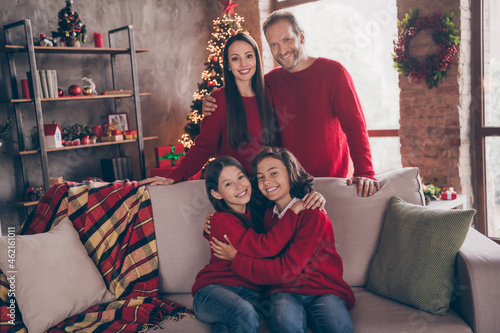 Photo of family brother sister hug rest sit on couch wear red pullovers jeans indoors at new year