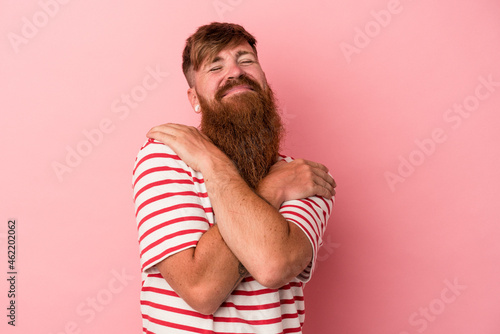 Fotografie, Obraz Young caucasian ginger man with long beard isolated on pink background hugs, smiling carefree and happy