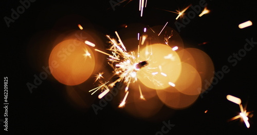 Lit party sparkler sparkling on black background