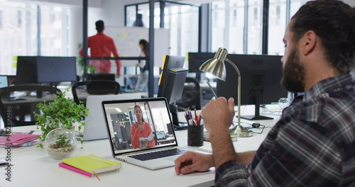 Middle eastern man having a image call with female colleague on laptop at office