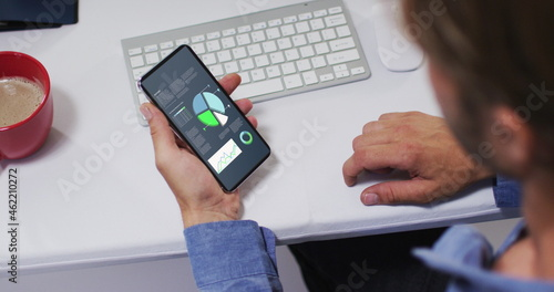 Caucasian man sitting at desk using smartphone with statistics on screen
