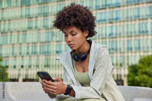 People and sporty lifestyle concept. Afro American young woman holds modern smartphone checks notification checks activity during break after workout browses internet poses against modern building