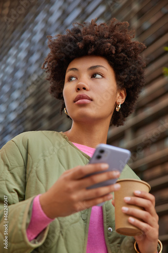 View from above of young Afro American curly woman drinks aromatic beverage holds mobile phone for chatting online dressed in casual clothes walks outside returns home after studying or work