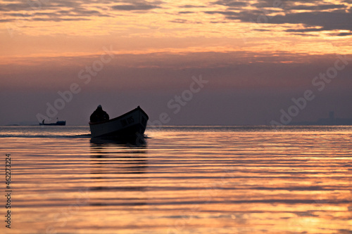 Fotografiet Silhouetted fishing boat on the calm sea at sunset