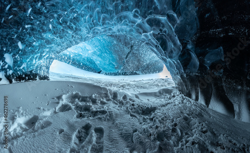 Fotografie, Obraz Blue crystal ice cave entrance and an underground river beneath the glacier loca