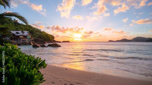 Fotografie, Obraz Romantischer Sonnenuntergang am Strand Anse Takamaka Beach mit Blick auf Chez Ba
