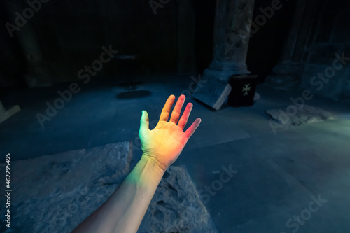 Tela A ray of sunlight fell on the hand of a believer in the interior of a Catholic church, decomposed into a rainbow spectrum of colors