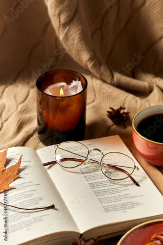 autumn, season and leisure concept - open book of poems with glasses, cup of coffee and candle in holder burning on warm blanket at home