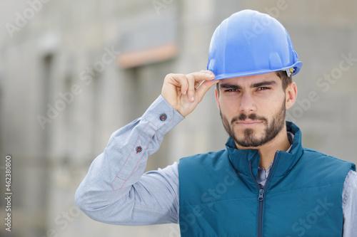 handsome bearded builder with protective helmet