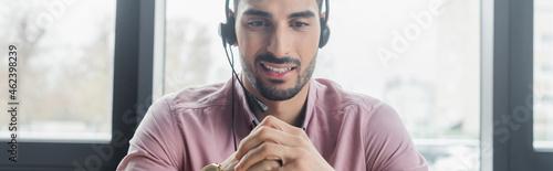 Obraz na plátně Smiling muslim businessman in headset in office, banner