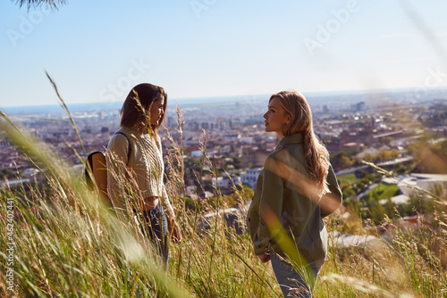 Fotografie, Obraz Two female friends having a chat on a hilltop