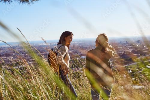 Fototapeta Two friends having a chat on a hilltop
