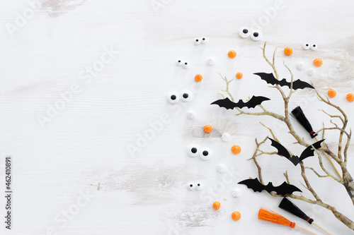 top view image of Halloween holoday. witcher broom, bare trees, treats and bats over white wooden table