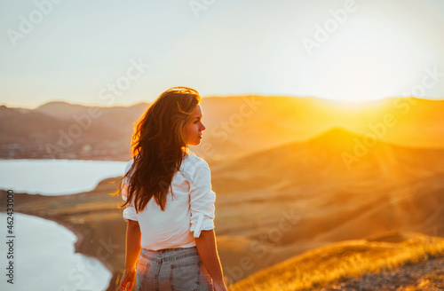 Wallpaper Mural A young woman travels along the mountain coast at sunset