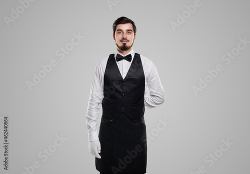 Photo Bearded waiter in uniform on gray background